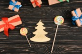 top view of lollipops, fir tree symbol and christmas gifts on wooden surface