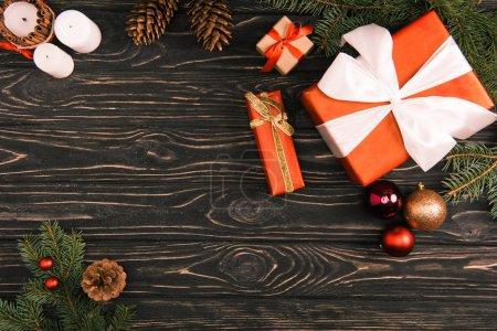 Foto de Vista superior de cajas de regalo, bolas de Navidad y ramas de abeto en la superficie de madera - Imagen libre de derechos
