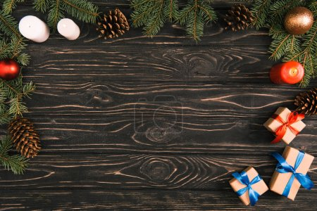 top view of christmas presents, candles and fir twigs with baubles and pine cones on wooden surface