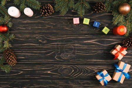 top view of 2019 symbol on cubes, christmas gifts, candles and fir twigs with baubles and pine cones on wooden surface