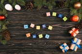 top view of merry xmas lettering on cubes and gift boxes with fir twigs on wooden surface