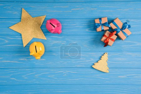 top view of yellow and pink piggy banks, star, christmas tree symbol and gift boxes blue wooden surface