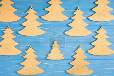 top view of decorative christmas trees on blue wooden surface