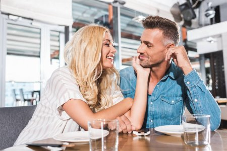 smiling girlfriend touching boyfriend face at table in cafe