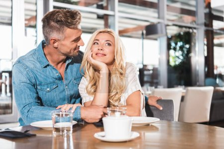 handsome boyfriend looking at pensive smiling girlfriend at table in cafe