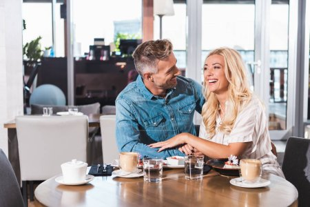 happy laughing couple holding hands and spending time at table in cafe
