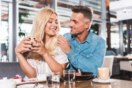 boyfriend hugging smiling girlfriend and she holding cup of coffee at table in cafe