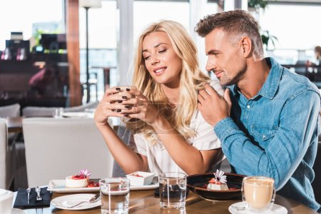 boyfriend hugging cheerful girlfriend and she holding cup of coffee at table in cafe