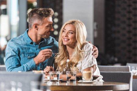 happy boyfriend feeding girlfriend with tasty dessert at table in cafe