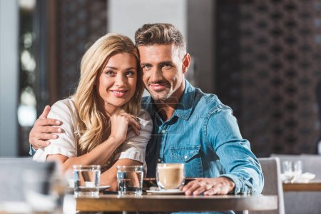 Photo for Happy tender heterosexual couple hugging at table in cafe and looking at camera - Royalty Free Image