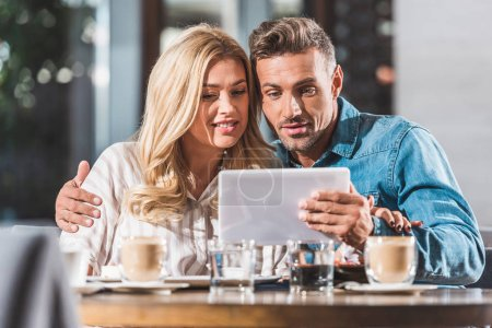 happy affectionate couple using digital tablet in cafe