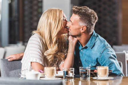 affectionate romantic couple kissing at table in cafe