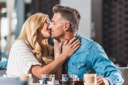 affectionate heterosexual couple kissing at table in cafe