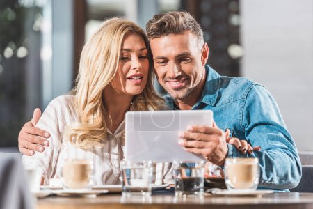 Photo for Girlfriend and boyfriend using tablet at table in cafe - Royalty Free Image