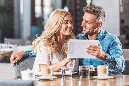 affectionate couple using tablet at table in cafe and looking at each other