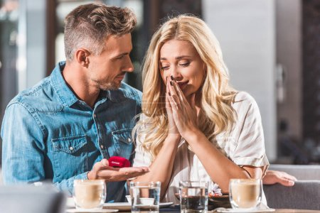 handsome boyfriend making proposal to surprised girlfriend and holding ring box in cafe
