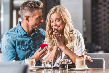 handsome boyfriend proposing surprised attractive girlfriend and holding ring box in cafe