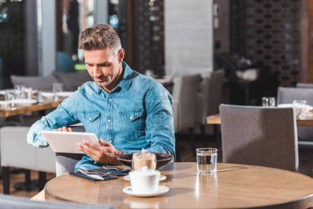 Photo for Handsome man using tablet in cafe - Royalty Free Image