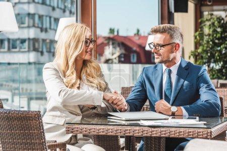 Photo pour Portrait de partenaires d'affaires serrant la main sur une réunion d'affaires dans un café - image libre de droit