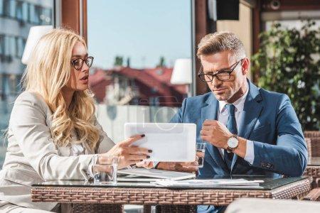Photo pour Portrait de gens d'affaires utilisant une tablette tout en discutant du projet sur la réunion dans le café - image libre de droit
