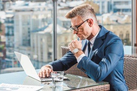 Foto de Vista lateral del hombre de negocios enfocado en anteojos usando computadora portátil en la mesa con vaso de agua en la cafetería - Imagen libre de derechos