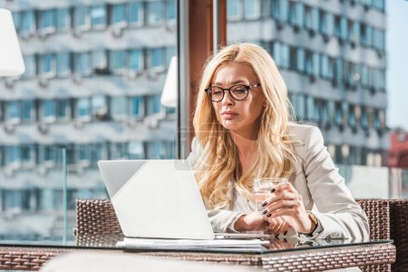 blond businesswoman in eyeglasses using laptop in cafe