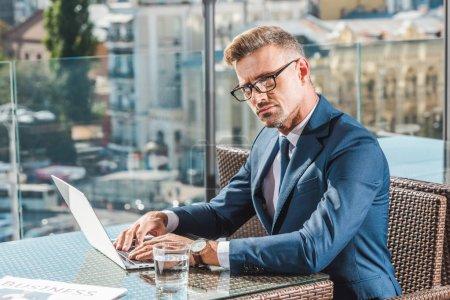 Photo pour Homme d'affaires confiant en lunettes assis à table avec ordinateur portable et le verre d'eau au café - image libre de droit