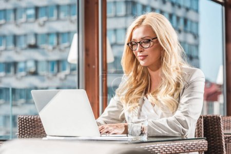 smiling blond businesswoman in eyeglasses using laptop in cafe