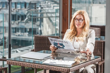 portrait of beautiful blond businesswoman with glass of water reading newspaper in cafe