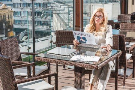 Foto de Empresaria con vaso de agua leyendo el periódico en la mesa de café - Imagen libre de derechos