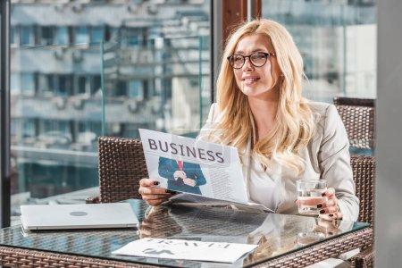 Foto de Retrato de empresaria sonriente con vaso de agua leyendo el periódico en la mesa de café - Imagen libre de derechos