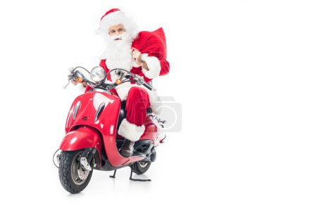 confident santa claus in costume holding christmas sack and riding on scooter isolated on white background