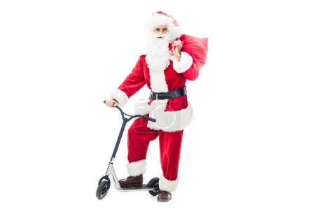 santa claus in costume standing on kick scooter and holding chirstmas sack over shoulder isolated on white background