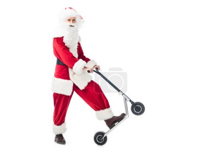 smiling santa claus in costume standing with kick scooter isolated on white background