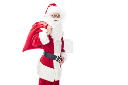 cheerful santa claus in eyeglasses holding christmas sack over shoulder isolated on white background