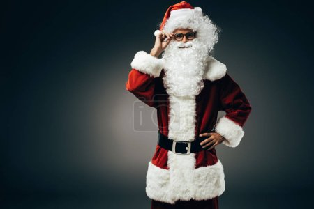 smiling santa claus in costume adjusting eyeglasses isolated on grey background