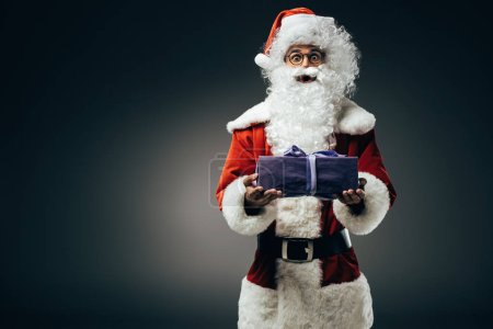 Photo for Surprised santa claus in costume holding gift box isolated on grey background - Royalty Free Image