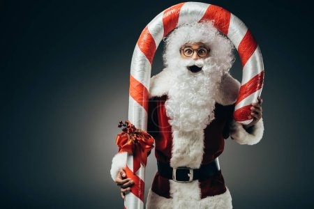 surprised santa claus in costume standing with big striped christmas stick isolated on grey background