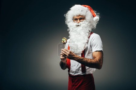 Photo for Happy santa claus in eyeglasses standing with colorful lollipop isolated on grey background - Royalty Free Image