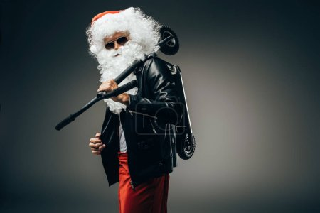 stylish santa claus in sunglasses and leather jacket holding kick scooter over shoulder isolated on grey background