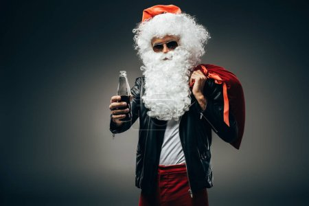 stylish santa claus in sunglasses and leather jacket showing bottle of cream soda and holding christmas bag over shoulder isolated on grey background