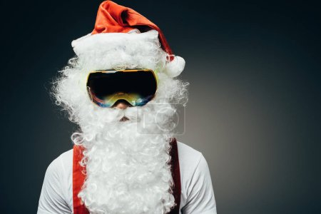 portrait of santa claus in ski mask standing isolated on grey background