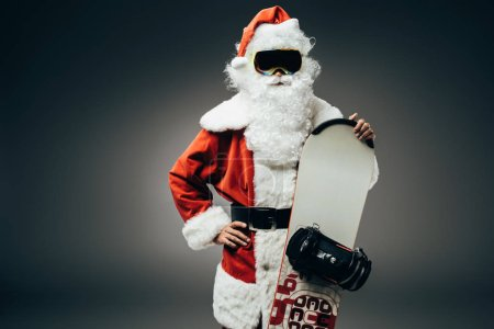 confident santa claus in ski mask standing with hand on waist and holding snowboard isolated on grey background