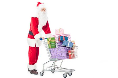 side view of santa claus carrying trolley with pile of gift boxes isolated on white background