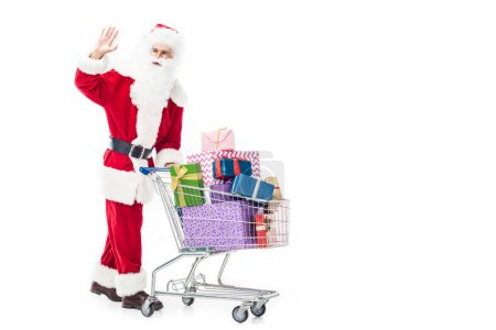 Photo for Santa claus waving by hand carrying trolley with pile of gift boxes isolated on white background - Royalty Free Image