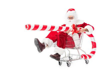 santa claus holding big striped christmas stick in trolley isolated on white background