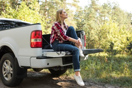 side view of young woman sitting in trunk of pick up car outdoors