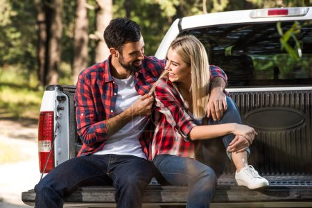 smiling young couple embracing and sitting on car trunk outdoors
