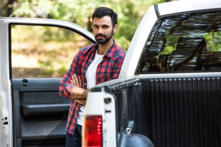 selective focus of young man standing with crossed arms near pick up car outdoors