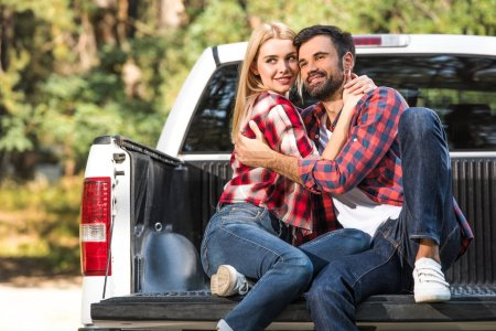 happy young couple embracing each other on car trunk outdoors